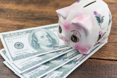 Piggy bank and money. On wood background Royalty Free Stock Image
