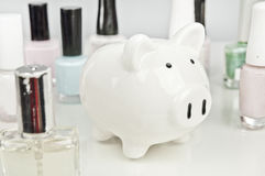 Piggy bank and nail polish - saving on cosmetics Stock Photos