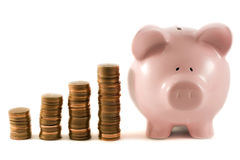 Piggy bank next to 'graph' of coins. Piggy bank next to stacks of copper coins Stock Images