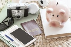 Piggy bank next to a passport, a smartphone, a camera and some stuff ready for a touristic travel. Empty copy space. For Editor`s text royalty free stock photography