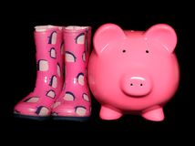 Piggy bank next to wellies royalty free stock images