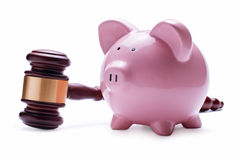 Piggy bank next to a wooden judge gavel Stock Photo