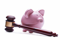 Piggy bank next to a wooden judge gavel Royalty Free Stock Image