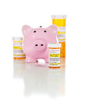 Piggy Bank and Non-Proprietary Medicine Prescription Bottles Iso. Lated on a White Background royalty free stock image