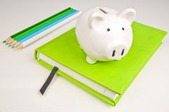 Piggy bank, notebook, blue and green pencils Royalty Free Stock Photo