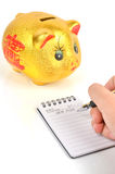 Piggy bank and notepad Royalty Free Stock Image