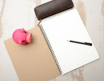 Piggy bank and notepad on a table Stock Photos