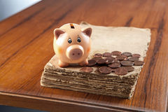 Piggy bank on old book Stock Photo