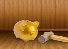 Piggy bank and old hammer on wood background. Stock Photo
