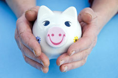 Piggy bank in the old woman hands Royalty Free Stock Image