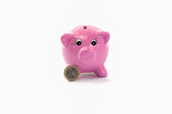 Piggy bank with one euro coin. Pink ceramic piggy bank with one euro coin isolated on white Royalty Free Stock Photos