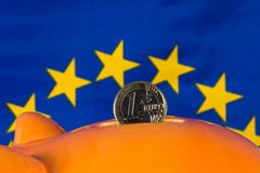 Piggy bank with one euro coin, EU flag in background. Close up of Piggy bank with one euro coin, EU flag in background Stock Photo