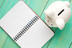Piggy bank and open notebook. Royalty Free Stock Photography