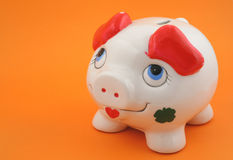 Piggy bank on orange Stock Images