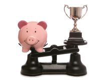 Piggy bank out weighing trophy Royalty Free Stock Images