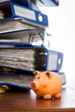 Piggy bank over stack of folders Stock Photos