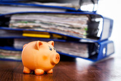 Piggy bank over stack of folders Stock Photography