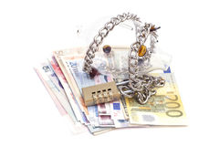 Piggy bank padlocked with chains and padlock on euro banknotes Stock Photos