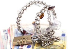 Piggy bank padlocked with chains and padlock on euro banknotes Royalty Free Stock Images