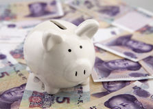 Piggy bank on a pile of china five yuan banknotes Royalty Free Stock Photo