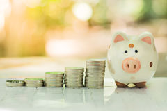 Piggy bank with a pile of coinsใ. Piggy bank with a pile of coins Royalty Free Stock Photography
