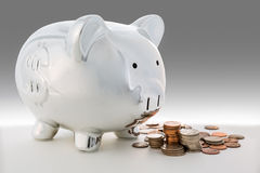 Piggy bank and a pile of coins Royalty Free Stock Images