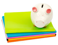Piggy bank on pile of copybooks. On isolated white background, side view Stock Photos