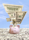 Piggy bank in a pile of dollars Royalty Free Stock Photography