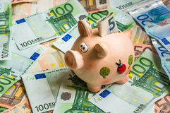 Piggy bank in a pile of euro money Stock Photos