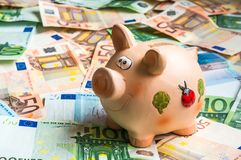 Piggy bank in a pile of euro money Stock Photo
