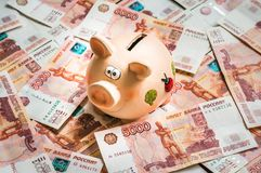 Piggy bank in a pile of russian five thousand banknotes Royalty Free Stock Image