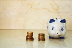 Piggy Bank and Piles of Coins. Piggy Bank looking at two piles of golden coins Stock Photo