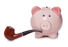 Piggy bank with a pipe Stock Images