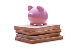 Piggy bank placed on the top of a pile of books Stock Photos