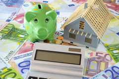 Piggy Bank and Pocket calculator on banknotes. Pocket calculator with blank display. Green Piggy Bank and a model of a new building on a background of Euro Royalty Free Stock Image