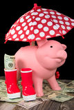 Piggy bank with polka dot umbrella Stock Photo