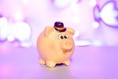Piggy bank on purple blurred background, concept of saving money royalty free stock photos