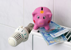 Piggy bank with radiator thermostat saving heating costs. Save energy / Piggy bank with euro banknotes next to a thermostat on the heating Stock Photo