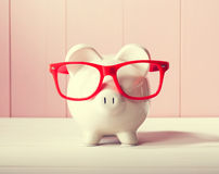Piggy bank with red glasses Royalty Free Stock Photo