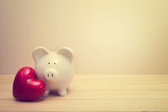 Piggy bank with red heart Stock Photos