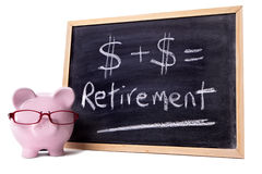 Piggybank with retirement calculation, pension fund growth planning concept. Pink piggy bank with glasses standing next to a blackboard with simple retirement Royalty Free Stock Photos