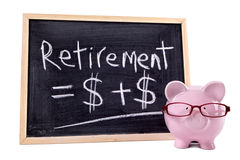 Piggy Bank wearing glasses with retirement growth formula, old age planning concept. Pink piggy bank with glasses standing next to a blackboard with simple Royalty Free Stock Photo