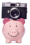 Piggy bank with retro camera cutout Royalty Free Stock Photography