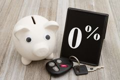 A piggy bank with retro freestanding chalkboard with car key on. Weathered wood with text 0 stock photos