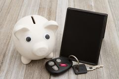 A piggy bank with retro freestanding chalkboard with car key on. Weathered wood that is blank for your message royalty free stock images