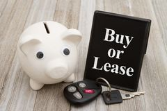 A piggy bank with retro freestanding chalkboard with car key on. Weathered wood with text Buy or Lease royalty free stock photo