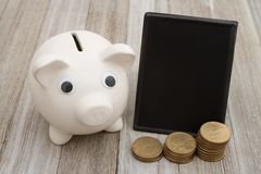 A piggy bank with retro freestanding chalkboard with gold coins. On weathered wood that is blank for your message stock photos