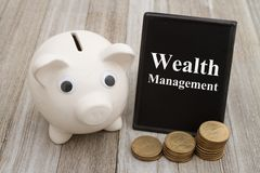 A piggy bank with retro freestanding chalkboard with gold coins on weathered wood. With text Wealth Management royalty free stock photography