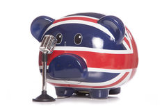 Piggy bank with retro microphone Stock Images