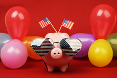 Piggy bank with retro sunglasses with USA flag and two small USA flags and balloons many colors on red background Stock Photo
